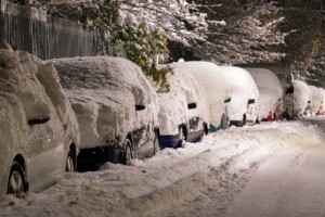 A photo of cars with lots of snow on top.