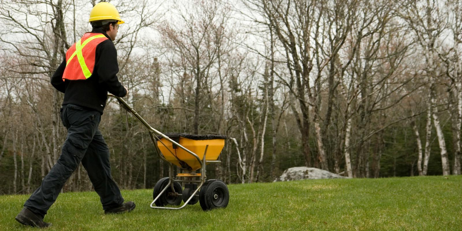 Lawn care worker spreads fertilizer