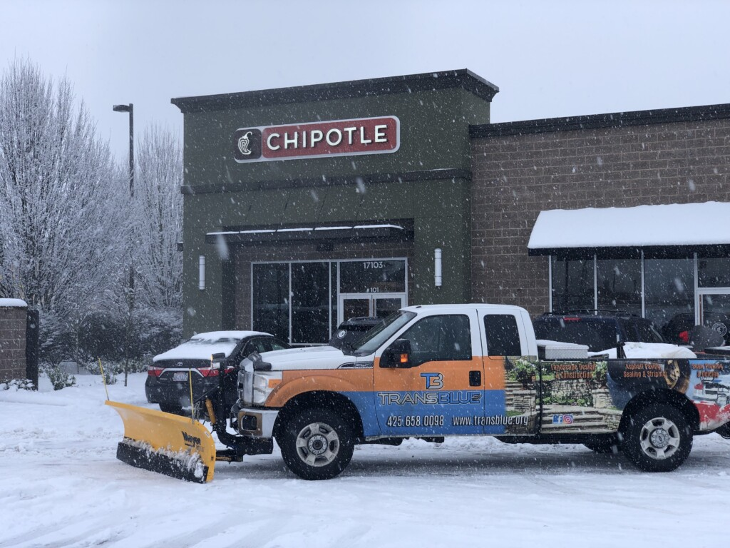 A transblue snowplow outside of a Chipotle store.