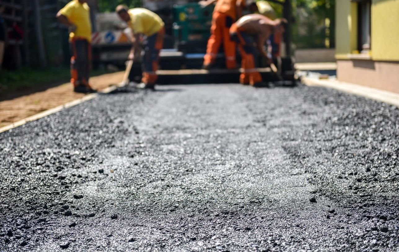 A photo of workers laying down asphalt.